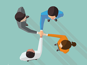 four business people holding hands in circle