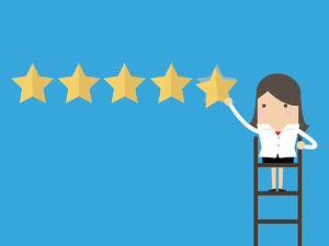 recruiter standing on ladder hanging five stars on a wall