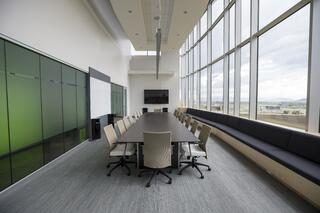 Conference room, green wall, long table with white chairs.