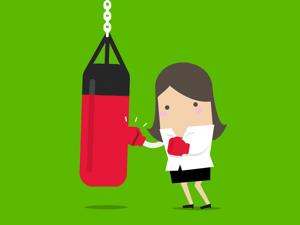 Woman hitting punching bag.
