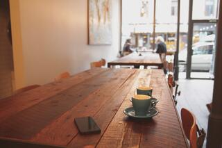 Smartphone, coffee cups, wooden table, in a coffee shop.